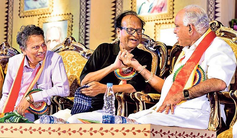 Writer Chandrashekhar Patil and BJP state president BS Yadiyurappa is sharing a light moment at the  Valedictory program of 82th Kannada Sahitya Sammelana in Raichur on Sunday. Sammelana President Baragooru Ramachandrappa is seen. -Photo by KRISHNAKUMAR P S